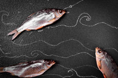 Three dried in the salt fish ram on the black surface Royalty Free Stock Photo