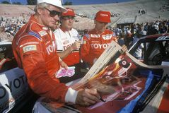 Three drivers sign posters at an off-road truck racing event at the Rose Bowl in Pasadena, California, ca. 1993 Royalty Free Stock Images