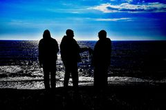 Three drunks silhouette by the sea stock images