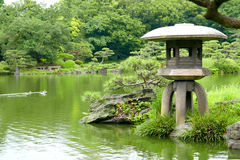 Three ducks and stone lantern in zen garden pond Stock Photo