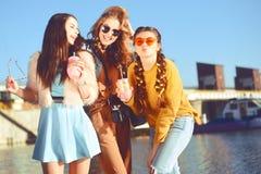 =Three dziewczyny blisko rzeki przeciw niebu ma zabawę Mod dziewczyny w okularach przeciwsłonecznych Skok, raduje się, pije, napo zdjęcia stock