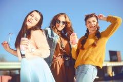 =Three dziewczyny blisko rzeki przeciw niebu ma zabawę Mod dziewczyny w okularach przeciwsłonecznych Skok, raduje się, pije, napo zdjęcia royalty free