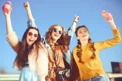 =Three dziewczyny blisko rzeki przeciw niebu ma zabawę Mod dziewczyny w okularach przeciwsłonecznych Skok, raduje się, pije, napo obrazy royalty free
