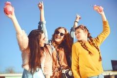 =Three dziewczyny blisko rzeki przeciw niebu ma zabawę Mod dziewczyny w okularach przeciwsłonecznych Skok, raduje się, pije, napo obraz royalty free