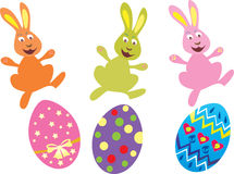 Three Easter bunnies and Easter eggs. Three brightly colored Easter bunnies jump over brightly decorated Easter eggs Royalty Free Stock Images