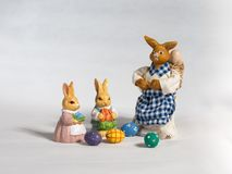 Three easter bunnies. Mother and child`s with basket and eggs. Three happy easter bunnies with basket and colored easter eggs. Mother and two child`s Royalty Free Stock Images