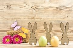 Three easter bunnies and two easter eggs. With flowers and butterflies Royalty Free Stock Image