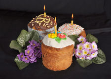 Three easter cakes and flowers  on the table. Three easter cakes and flowers cost on a black table Royalty Free Stock Image