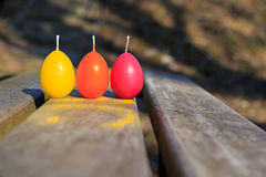 Three Easter candles in the shape of eggs on the wooden bench Stock Photo