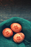 Three Easter chicken brown eggs in a nest of green color from fabric Stock Image