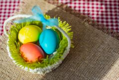Three Easter eggs in a basket on a burlap napkin royalty free stock photo