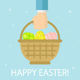 Three Easter eggs in basket. Basket with colorful Easter eggs in hand on blue background, illustration Royalty Free Stock Photo