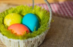 Three Easter eggs in a basket stock images