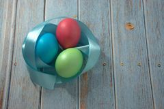 Three Easter eggs with a blue satin ribbon lie on a wooden table stock image