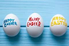 Three Easter eggs with color titles `Happy Easter` written by paint brush are on the blue colored wooden background.  Stock Photo