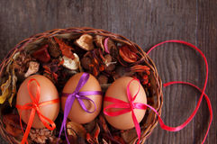 Three Easter eggs are decorated bright with color tapes in a basket with dry flowers Stock Photo
