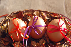 Three Easter eggs are decorated bright with color tapes in a basket with dry flowers Stock Photos