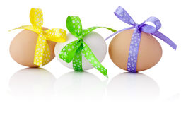 Three Easter eggs with festive bow isolated on white background Stock Photos