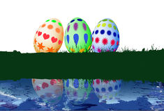 Three Easter eggs on grass with a water reflection Royalty Free Stock Image
