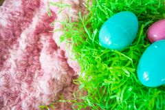 Three Easter eggs on green plastic grass and pink background stock images