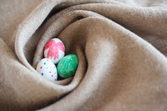 Three Easter eggs in a nest. Of burlap Royalty Free Stock Photos