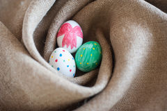 Three Easter eggs in a nest. Of burlap Royalty Free Stock Photography