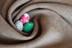 Three Easter eggs in a nest. Of burlap Stock Photos