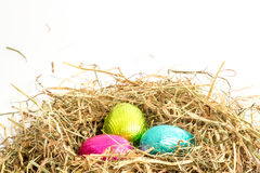 Three easter eggs nestled in straw nest Royalty Free Stock Photo
