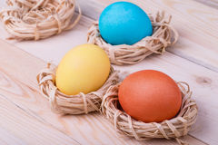 Three Easter eggs in small nests Stock Photos