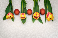 Three Easter eggs and tulips. Royalty Free Stock Photography