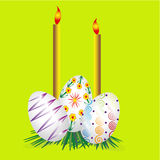 Three Easter eggs and two candles Stock Photography