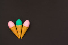 Three Easter eggs in waffle cones on a black background. royalty free stock photo