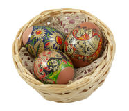 Three Easter eggs in a wicker basket over a white Royalty Free Stock Image