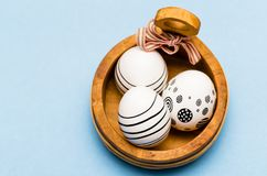Easter background with three painted eggs with black stripes. Three Easter eggs in a wooden container from above on blue background and empty space Royalty Free Stock Photos