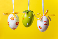 Three Easter eggs. On a yellow background stock photos
