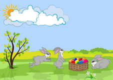 Three Easter rabbits and basket with color eggs. Royalty Free Stock Photos