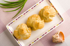 Three eclairs on a square plate. Three cream puffs on a square plate. Close up shoot stock photos
