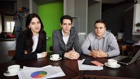 Portrait of three successful male and female students or colleag. Three educated employees of company, two guys and girl look with smile at camera and pose, are Stock Photo