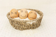 Three egg in a brown Basket on rice. And happy,sad,angry egg stock photos
