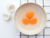 Three egg yorks with egg shell on tablecloth Royalty Free Stock Photography
