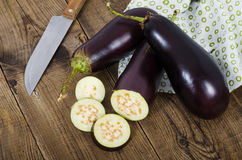 Three eggplants with cut off pieces on wood planks. Three eggplants, cut off piecesand knife on dark wood planks Royalty Free Stock Photo