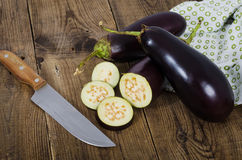 Three eggplants and knife on wood planks. Three eggplants, cut off pieces and knife on dark wood planks Royalty Free Stock Photo