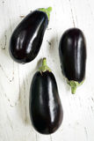 Three Eggplants on White Timber Royalty Free Stock Photo