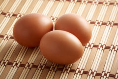 Three eggs. On kitchen on bamboo rug Royalty Free Stock Image