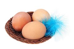 Three eggs in a basket and feather. Three eggs in a basket and a feather isolate Royalty Free Stock Photography