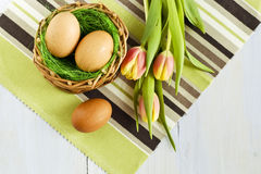 Three eggs in a basket and tulips Stock Photo