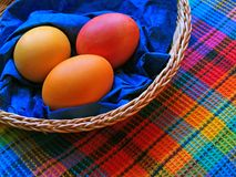 Three eggs in the baskets on checkered fabric. Three colored easter eggs in the baskets on checkered fabric Royalty Free Stock Photography