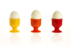 Three eggs in colorful egg cups Stock Photo