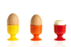 Three eggs in colorful egg cups Stock Photos