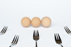 Three eggs and five forks on a white background Stock Images